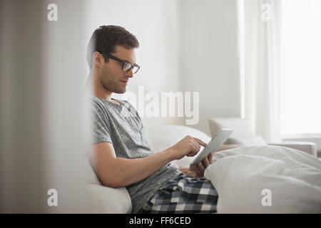 A working day. A man sitting in bed using a digital tablet with touchscreen. - Stock Photo