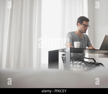 A working day. A man seated at a laptop computer, working in a hotel bedroom with a cup of coffee. - Stock Photo
