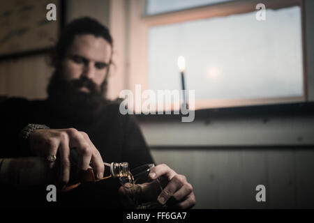 A man sitting alone in a room pouring himself a glass of whisky. A lit candle. - Stock Photo