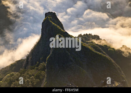 Sunrise over steep cliffs and peaks with the morning mist still covering bottom of the canyons and rugged valleys - Stock Photo