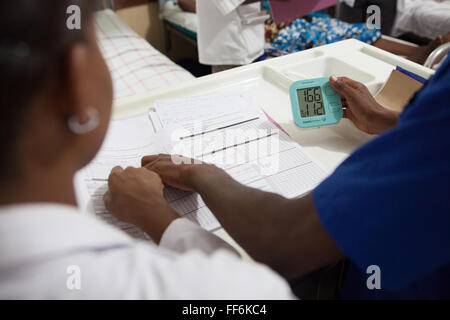 A doctor examining a blood pressure monitor, St. Francis Hospital, Tanzania. - Stock Photo