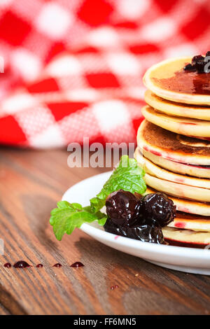 stack of pancakes on a white plate with cherry jam, mint leaves, red checkered napkin, brown wooden background of - Stock Photo