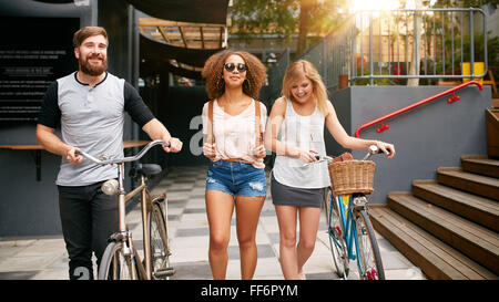 Three young people walking down the street with their bicycles. Male and female friends on road with their bike. - Stock Photo