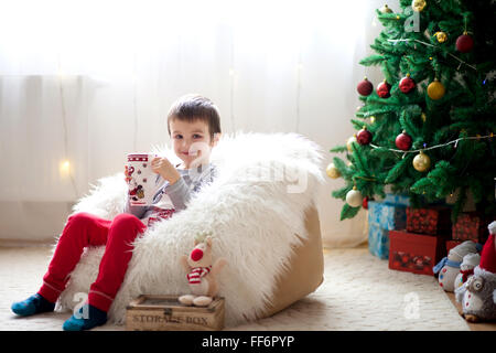 Cute boy, sitting on bean bag, drinking tea and enjoying Christmas holidays, Christmas decoration around him - Stock Photo