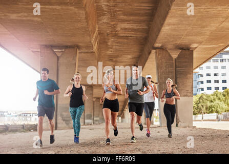 Group of athletes running on a road under bridge in the city. Young men and women jogging, training together in - Stock Photo