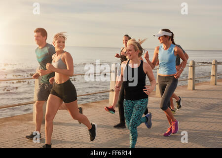 Portrait of young people running by the sea in morning, Healthy young men and women doing running workout. - Stock Photo