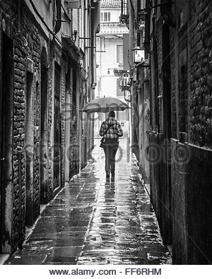 VENICE, ITALY -  18 FEBRUARY 2010:  Monochrome image of a woman walking through a Venice street with an umbrella - Stock Photo