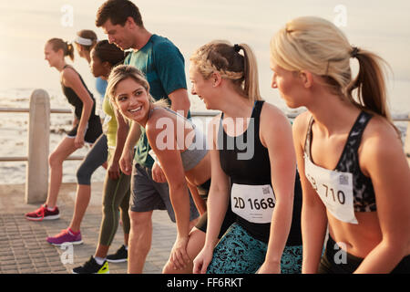 Happy young woman standing at starting line along with competitors. Racers standing at starting line of a marathon - Stock Photo
