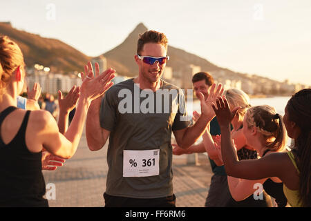 Group of young adults cheering and high fiving a male athlete crossing finish line. Sportsman giving high five to - Stock Photo
