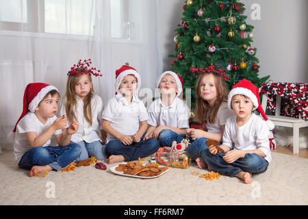 Six adorable children, having fun in front of the Christmas tree, eating candies and cookies - Stock Photo