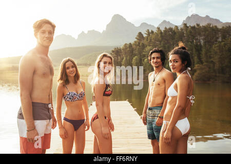 Portrait of young people in swimwear standing by a lake and looking at camera. Men in swimming trunks and women - Stock Photo