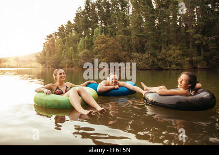 Portrait of happy young friends in inflatable rings floating on lake. Young people relaxing in water on a summer - Stock Photo