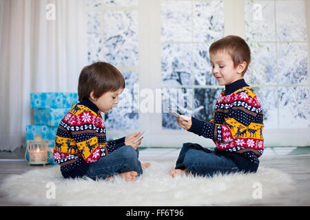 Two adorable children, boy brothers, playing cards at home, wintertime, christmas decoration around them, snowy - Stock Photo