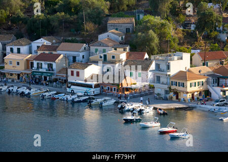 Loggos, Paxos, Ionian Islands, Greece. View over the harbour from hillside, coach edging slowly along narrow quay. - Stock Photo