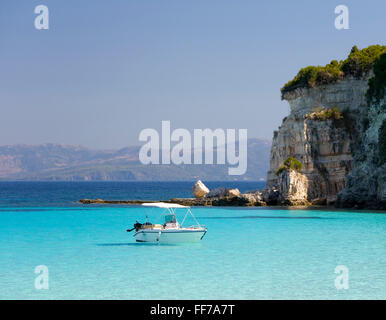 Antipaxos, Ionian Islands, Greece. View across secluded Voutoumi Bay, solitary boat at anchor. - Stock Photo