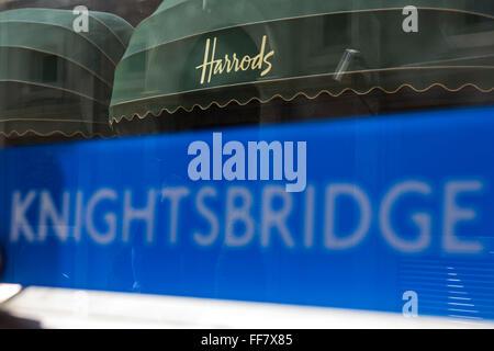 Knightsbridge London Underground sign outside the tube station entrance with the world famous Harrods shop awning - Stock Photo