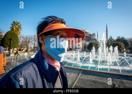 A Japanese tourist wearing a face-mask near the Sultan Ahmed Mosque in Istanbul, Turkey. - Stock Photo