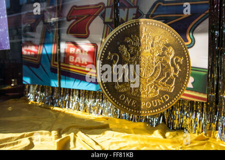 A large model of a British one pound coin in the window display of a Cashino amusement arcade in Lewisham, London, - Stock Photo