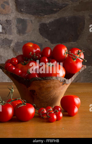 Wooden bowl of tomatoes on a table in a rustic kitchen - Stock Photo