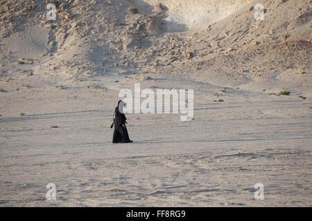 Lone Arab woman walking in Brouq Nature Reserve, Qatar desert in traditional dress, abaya, near a Gypsum plateau. - Stock Photo