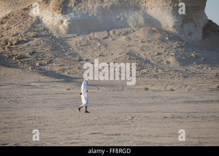 Lone Arab man walking in Qatar desert in traditional white robe, thawb, next to Gypsum plateau. - Stock Photo