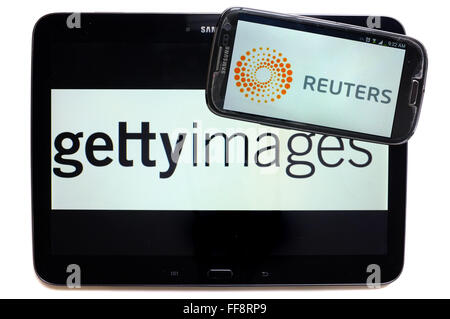 The news agencies getty images and Reuters on the screens of a tablet and a smartphone photographed against a white - Stock Photo