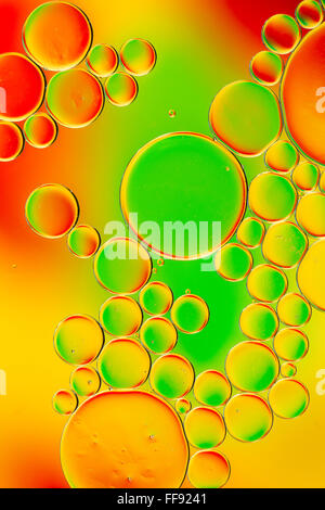 Oil on water with colourful background - Stock Photo