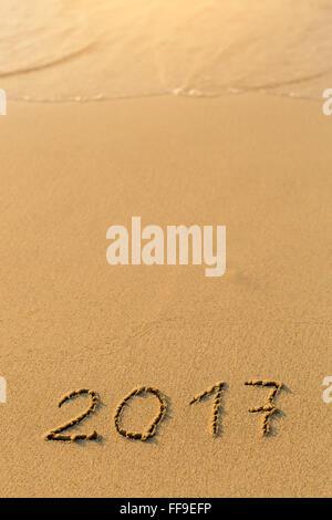 2017 - inscription on sand beach with the soft wave. - Stock Photo