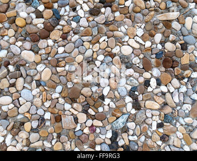 Colorful exposed aggregate concrete with gray, brown and blues pebbles in close-up - Stock Photo