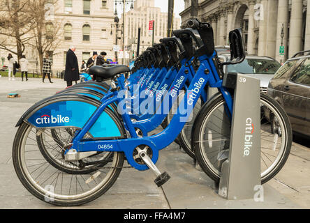 A row of blue Citi Bike bicycles lined up on the sidewalk in the docking station outside City Hall in New York City - Stock Photo