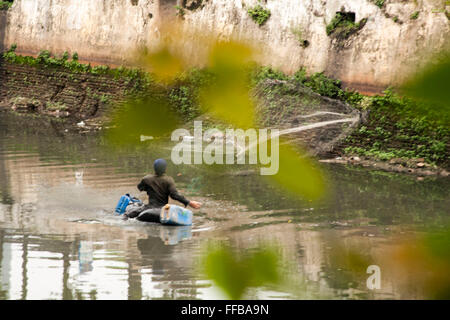 Jakarta, Indonesia. 11th Feb, 2016. Fish Hunter throwing nets at River in Jakarta, Indonesia. Fishes catch will - Stock Photo