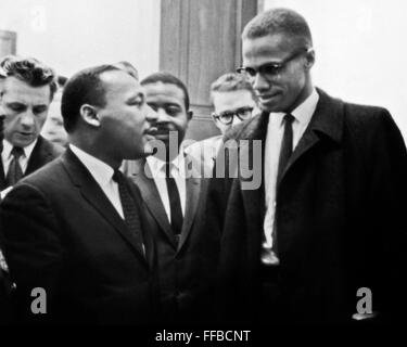 Reverend Martin Luther King and Malcolm X speak while waiting for press conference to begin. Photographed March - Stock Photo