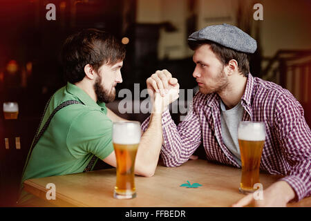 Two young men arm-wrestling while sitting in pub - Stock Photo