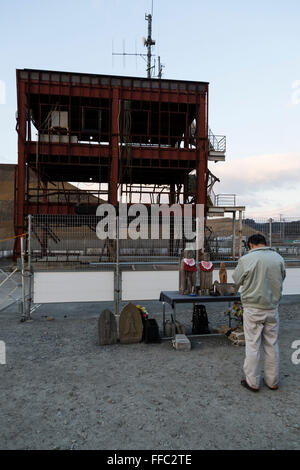 A man prays at the tsunami-wrecked Disaster Management Center five years after the 2011 Tohoku Earthquake and Tsunami - Stock Photo