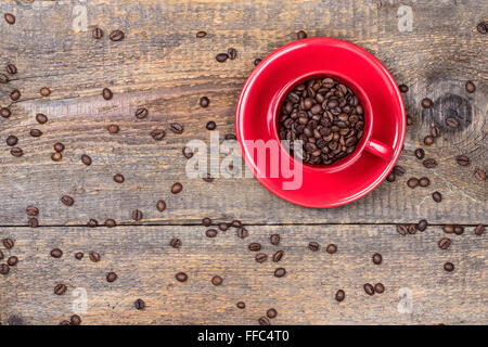 Coffee beans in red cup on wooden background - Stock Photo
