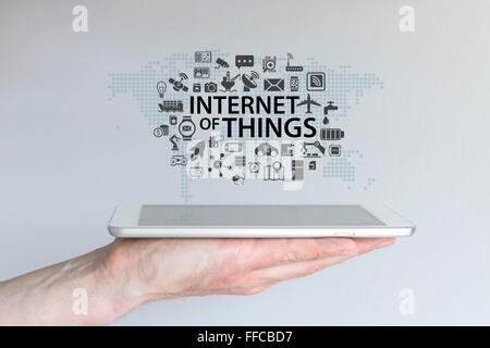 Hand holding tablet or modern smart phone. Internet of things (IOT) background concept. - Stock Photo