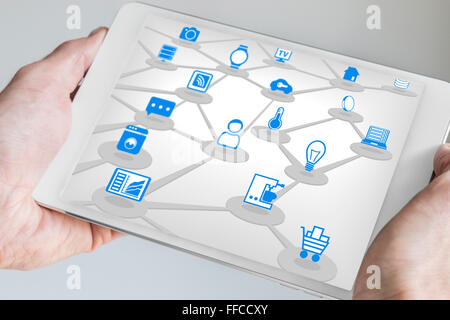 Male holding tablet in both hands with internet of everything (IOT) concept. Connected devices like sensors and smart phone.