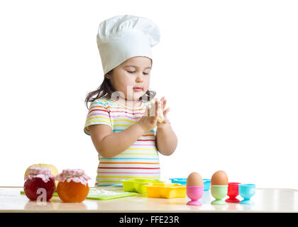 Child little girl kneading the dough for the cookies, isolated on white - Stock Photo