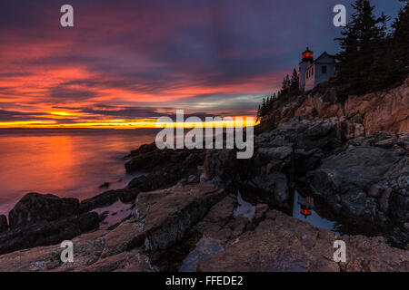 The iconic landmark, Bass Harbor Head Lighthouse reflected in a tidepool at sunset in Acadia National Park, Mount - Stock Photo