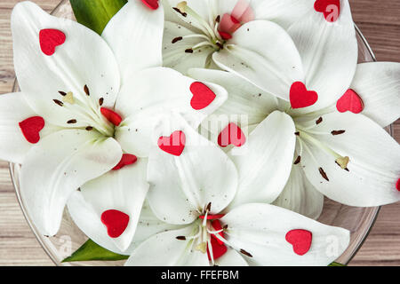 Arrangement of white lilies with more little red hearts in the glass bowl. Valentine's Day. Symbol of love. Closeup - Stock Photo