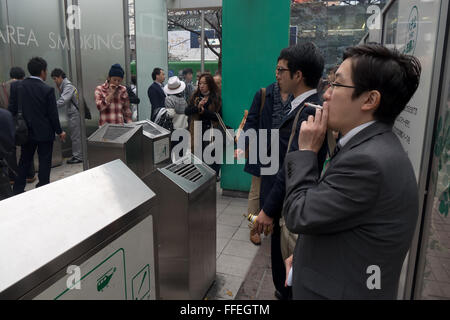 Japanese people with cigarette in the street, Asian smokers in smoking spot. Tokyo, Japan, Asia. Health issues, - Stock Photo
