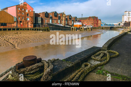 River Hull at low tide with an obsolete ship aground in the mud bank flanked by office and other buildings on one - Stock Photo