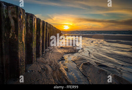 Sunset on St. Clements bay in Jersey. The light from the setting sun reflects beautifully on the wet sand and incoming - Stock Photo