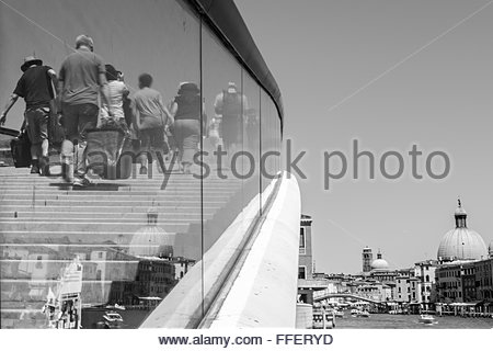 VENICE, ITALY -  10 JULY 2015:  Monochrome image of tourists crossing the glass-sided Calatrava Bridge. - Stock Photo