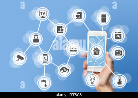 Home automation concept with hand holding modern smart phone to control home devices like a smart thermostat - Stock Photo