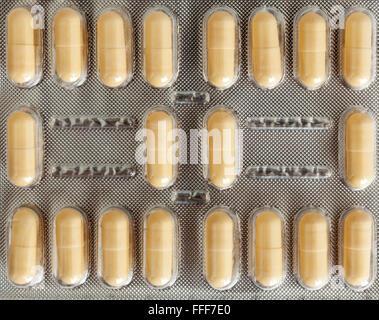 Orange capsules in blister pack on white background - Stock Photo