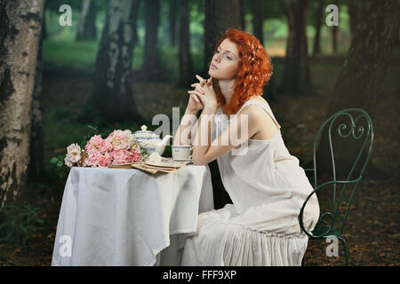 Beautiful redhead woman having tea in the forest . Romantic and victorian portrait - Stock Photo