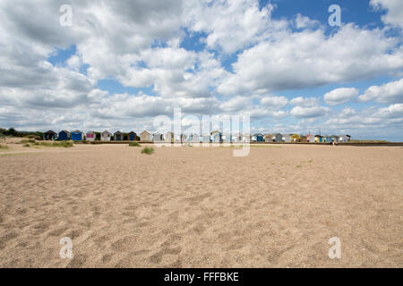 Row of traditional English beach huts with lots of clouds and sand, North Sea, Sutton-on-Sea, Lincolnshire, England, - Stock Photo