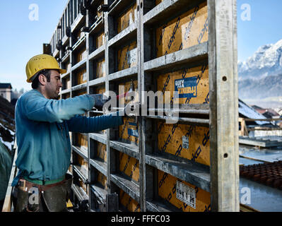 Construction worker hitting connecting element with hammer, shuttering wall, Innsbruck Land, Tyrol, Austria - Stock Photo