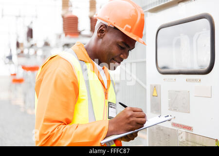 handsome African industrial technician taking machine readings - Stock Photo